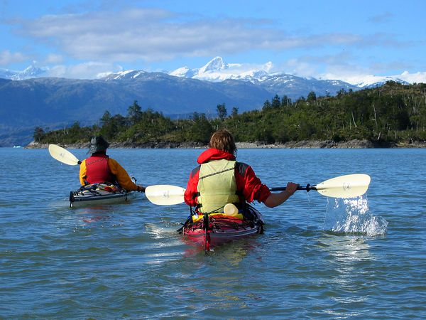 Students sea kayaking through Patagonia gaze at snow capped mountains in the distance.