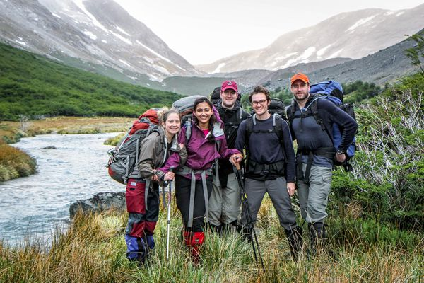 Students smiling together by a stream while backpacking in the Aysén region of Chile.