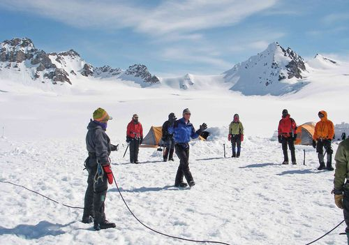 Course participants circle-up to listen to an instructor while mountaineering in Alaska.
