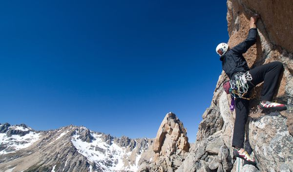 A student rock climbs near snow dusted peaks in Patagonia.