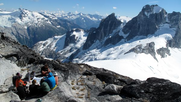 Students consult a map while sitting on a rocky ridge surrounded by snowy peaks in the rugged North Cascades.