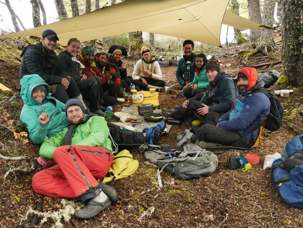 Smiling course participants gather together under a rain tarp for a meal in Patagonia.