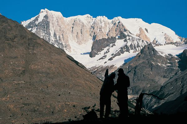 Two silhouetted students in the mountains of Patagonia practice route-finding while looking out at craggy snow-crusted peaks.