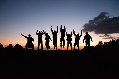 Students jump into the sunset after a long day hiking.
