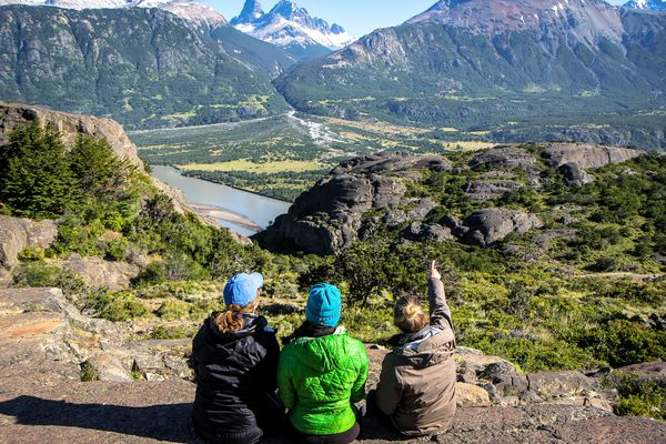 Several students sitting high up on a hill point to snow-capped peaks off in the distance in Patagonia.