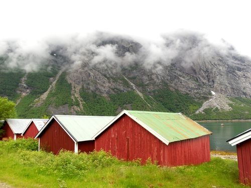 Several small red huts lined up next to a lake in Scandinavia.